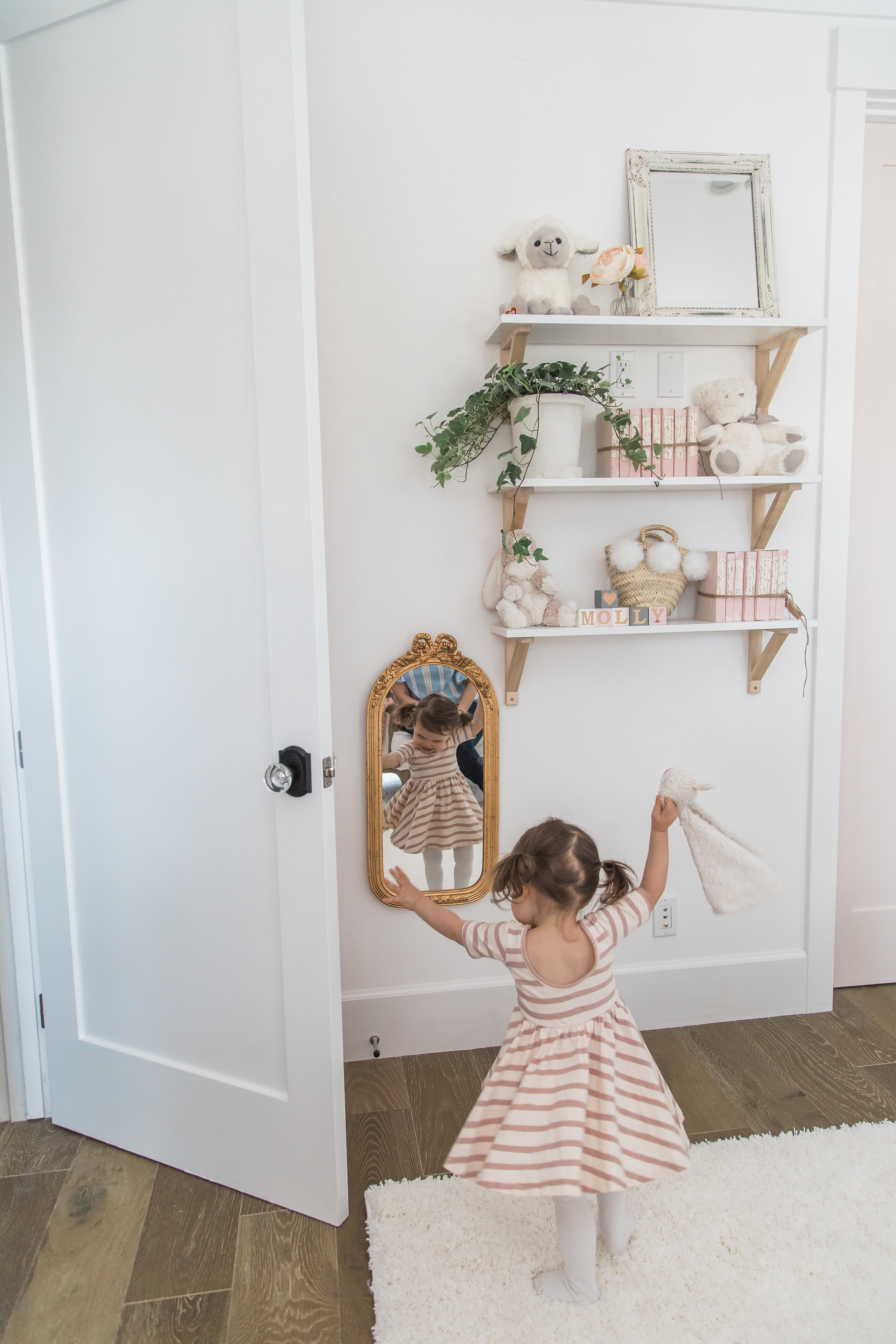 Child playing in bedroom with Schlage Custom Hobson Glass Knobs on the door.